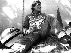 A dejected Senna slumps against the barrier after crashing out.