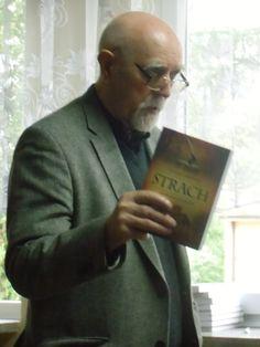 Autor Stanisław Srokowski trzyma w ręku książkę pt. Strach.
