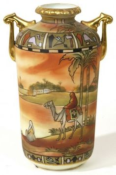 """NIPPON (1908- ), handled vase, Egyptian theme, dessert scene with man riding camel, hieroglyph frieze at shoulder and base, signed NIPPON with """"M"""" in wreath mark, 8"""" h."""