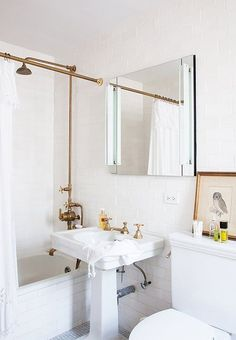 The all-white bathroom is an oasis of porcelain and metal thanks to the subway tiles and the custom unlacquered brass shower. The goal was to keep the room uncluttered and sleek.