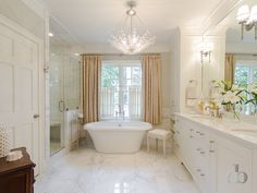 Transitional bathroom features a crystal chandelier over a freestanding tub placed under window dressed in peach short curtains layered over white sheer cafe curtains with a slim brass and glass table to the left and a French stool to the right.