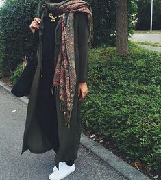 Pinterest: @eighthhorcruxx. Black outfit with khaki open abaya, patterned scarf and white trainers