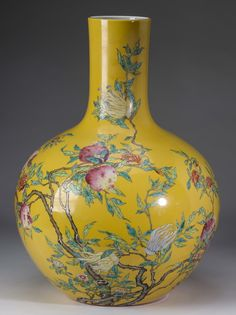 "Chinese famille rose bottle vase, having a stick neck above a globular body decorated with pomegranates, Buddha's hand citron, and butterflies all on a yellow ground, conveying the meaning 'May you have many successful sons,' the underside with a red six character Qianlong mark, 21""h x 13.5""w."