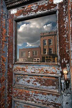 Broadway reflections by Pam  Fletcher, via 500px| Afternoon clouds reflect off of a cool old door on Broadway, uptown Butte, Montana.