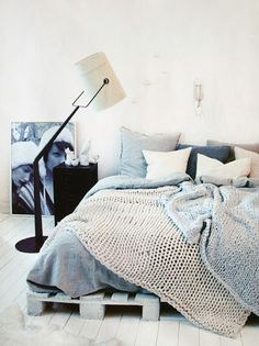love the over sized knit blankets, white wood floor, and floor lamp