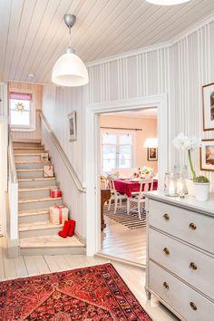 Huutokaupasta ostetussa eteisen lipastossa on kaunis, alkuperäinen väritys. Eeva ottaa punaiset itämaiset matot aina jouluksi esille vintiltä. Kesäksi ne vaihdetaan vaaleampiin kesämattoihin. Lasipurkit ovat talon vanhoja aarteita. Valaisimet Ikeasta.