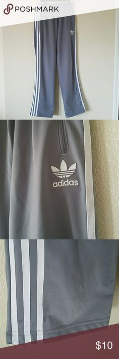 Adidas gray jogging pants for girls size 10/12 Addidas gray jogging pants for girls size 10/12// great condition// gray with white stripes on sides of legs and embroidered Addidas on side of hip// zipper front pockets adidas Bottoms