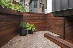 We built a custom backyard using ipe for it's durability and longevity. A built-in planter holds shade-tolerant plantings, lights built into the fence make the space more inviting after dark. A herringbone brick patio grounds the space and is made from recycled antique bricks. Patio Planters, Light Building, Brick Patios, Backyard Fences, After Dark, Rooftop, Design Projects, Landscape Design, Lights