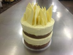 4 layered butter cake tower with butter cream icing and white chocolate on top