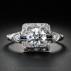 This is a stunning all original diamond engagement ring from the Art Deco period. A 1.00 carat European cut diamond is set within a square head and further set with a square diamond and synthetic sapphire border with a small accent diamond set into each pierced shoulder. Scrolled engraving decorates the shank.