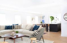 Neutral living room with bright dining room beyond