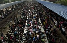 People ride an overflowing train at a railway station in Dhaka, Bangladesh
