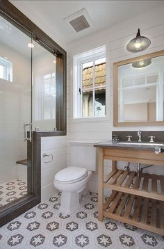 Shower doors, shower tiles, mosaic patterned floor, and the vanity style