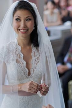 Happy bride in lace wedding gown by Renee L. Collections