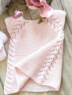 Free Knitting Pattern for Lil Rosebud Baby Dress - This seamless little top down dress / tunic top from OGE Designs is an easy knit, worked in garter stitch with a simple leaf pattern forming the front borders, then cascading down the sides.Sizes, 3 months — 6 months — 12 months — 18 months — 2 years — 4 years — 6 years