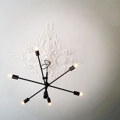 A mid-century modern inspired chandelier provides the perfect contrast to the 1850s plastered ceiling. Makes me happy every time I look up at it from the sofa...