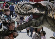 Japoneses observam estátua de dinossauro em exposição durante a Semana Dourada, em Tóquio - http://revistaepoca.globo.com//Sociedade/fotos/2013/05/fotos-do-dia-3-de-maio-de-2013.html (Foto: AP Photo/Itsuo Inouye)