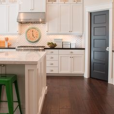 White shaker, backsplash, dark floor, mint green clock, dark gray pantry door