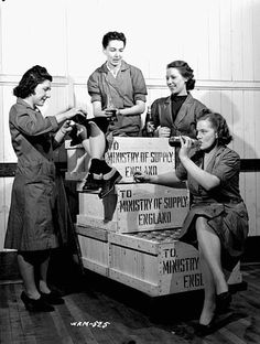 Group of female workers enjoying a break from their work of packing crates of 25-pounder field gun cases at a munitions plant    March 1941