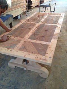 We first glued up a solid rough saw reclaimed wood top in a planked pattern and then added some hand distressing using a wood chisel. After, we used a orbital s