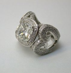 Large engagement ring with heart-like shapes formed on the sides