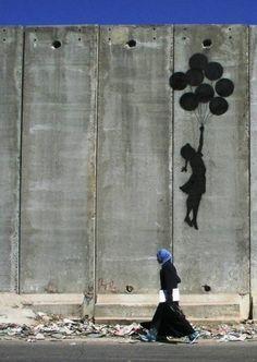 Banksy street art. Fotografía, sombra de niña con globos que vuela.