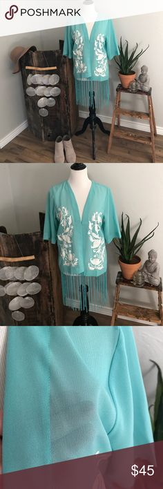 Turquoise fringe kimono I received this as a gift for my birthday last year and it has just sat in my closet. It is a beautiful turquoise color  kimono with white embroidery and fringe at the bottom. It is a one size fits all and could fit anywhere from a small to large or even extra large. It is 100% polyester and doesn't have any stretch. 24 inches to the bottom and 34 inches to the bottom of the fringe, 20 inches from pit to pit Crazy Train Tops