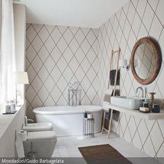 Das Rautenmuster der Tapete passt ausgezeichnet zu den Fliesen in weißer Parkettoptik. Natürliche Elemente liefern der Teppich aus Sisal, der Handtuchhalter aus …