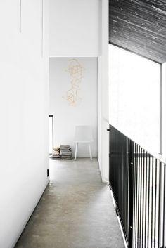 Black and white mezzanine hallway with concrete floor. Deko's housing-fair home Maja.
