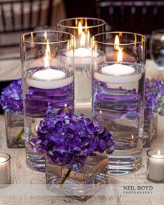 Purple hydrangea flowers and candles for wedding reception centerpiece.