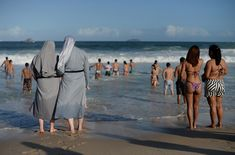 Two Polish nuns look at people bathing as hundreds of thousands of young Catholic pilgrims attending World Youth Day (WYD) start gathering at Copacabana beach in Rio de Janeiro for a prayer vigil with Pope Francis, on July 27, 2013.
