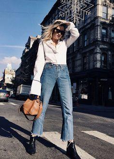 Street style look camisa branca, calça jeans com barra rasgada, bota preta e bolsa camelo.