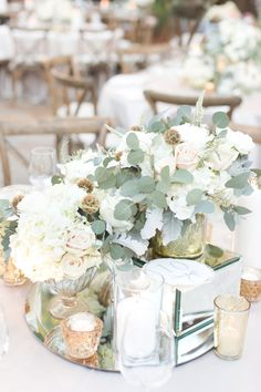 Country club wedding in a soft neutral color pallet. White and blush pink florals with eucalyptus leaves. Long wooden tables with with greens and flowers for runners.