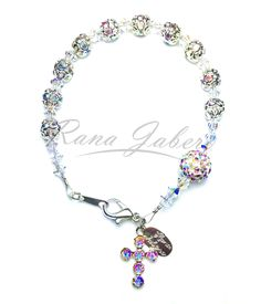 """This gorgeous Rosary bracelet features silver plated filigree beads that have iridescent Swarovski® rhinestones around and aurora borealis crystal beads in between. The larger """"Our Father"""" bead is cov"""