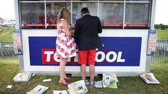 Racegoers place a bet on Derby Day 2015 at Epsom, Surrey.
