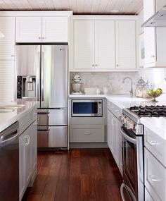 Gray lower cabinets, white uppers. Counter depth fridge, Marble back splash and counters, nice wood ceiling. Sarah Richardson