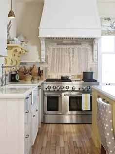 La Dolce Vita: Dissecting the Details: Sarah Richardson Kitchens. Neutral kitchen, white outer cabinets, cream or light yellow island, wood floor. Stainless or marble backsplash panel over stove.