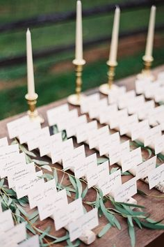 Rustic escort cards sitting in birch holder and brass candle holders behind