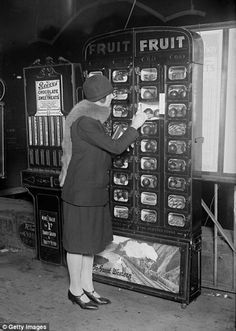 The World's Oldest and Oddest Vending Machines You Never Knew Existed - A woman buys fruit from a coin operated machine at Paddington Station in London, ca. 1920s.