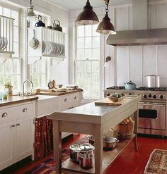 Cottage Kitchen: Love the TALL ceilings, big windows, natural lighting, the center prep island, the butcher block counters, the farmhouse sink, the big daddy stove, the red floors, etc., etc.