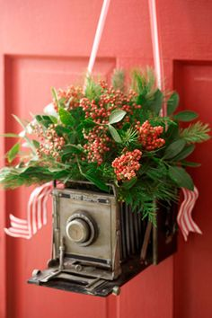 Want to show off your love of antiques? Hang a vintage camera from your front door and fill with flowers and other greenery. Add small cuts of ribbon for extra charm. See more at Petal Talk.