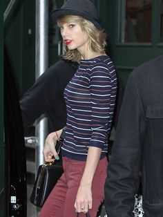 Taylor Swift in a striped long sleeve top, red pants and a black hat