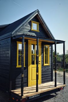 The outside of the 6-meter (~20-foot) home is pine treated with an eco-friendly black varnish. Yellow highlights include the front door, windows, and hand carved trim.