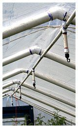 PVC greenhouse uses overhead sprinklers and 3/4 inch PVC ridge piece.