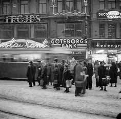 Stureplan 2-4. Folk väntar på buss/spårvagn i snöyran. I bakgrunden syns Hedengrens Bokhandel, Göteborgs Bank och Fröjds Herrkläder. Fotograf: Jan Ehnemark, 17 december 1955