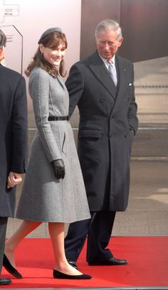 March 28, 2008 - Carla Bruni in Dior, with Prince Charles at Heathrow Airport.