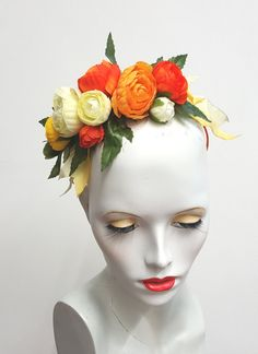 This pretty headband has been made using faux ranunculus flowers in tones of orange, yellow and ivory. Green leaves and yellow ombre wired ribbon