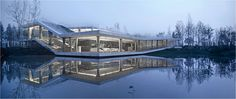 The clubhouse is located on one side of a river in Yancheng, surrounded by a park and sports field. The extended horizon, sky, water, island in river, and re...