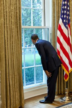 President Barack Obama looks out a window in the Oval Office at First Lady…