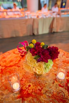 Yellow roses, burgundy dahlias, craspedia and gloriosa lilies add a spot of sunshine to these kiosk tables.